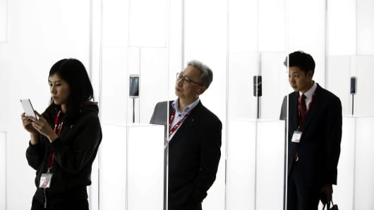 Visitors inspect the new Samsung Galaxy S6 Edge smartphones on display at the Mobile World Congress in Barcelona, Spain.