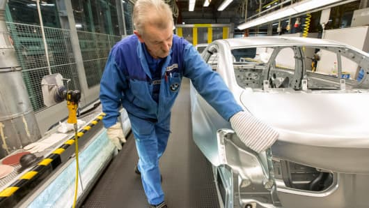 A worker checks the frame of a BMW automobile along the production line at the BMW plant in Munich, Germany.