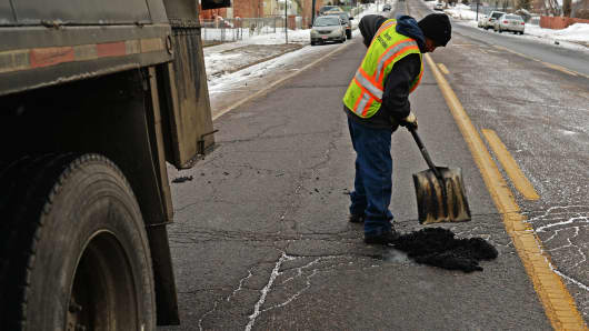 Sidney Oats of Denver Public Works patches a pothole at 2nd Avenue and Knox Court in Denver on March 3, 2015. The combination of unseasonably warm temperatures followed by freezing cold is responsible for the onslaught of potholes in the Denver area.