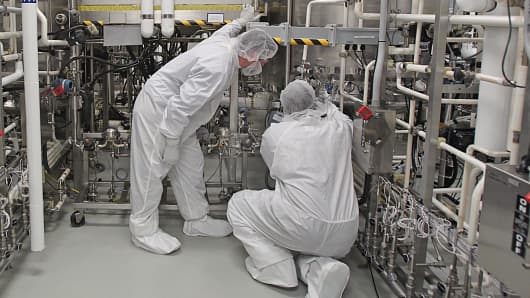 Biogen Idec employees work in the company's manufacturing room.