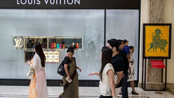 People walk past a LVMH Moet Hennessy Louis Vuitton SA store at the DLF Emporio shopping mall in New Delhi, India.