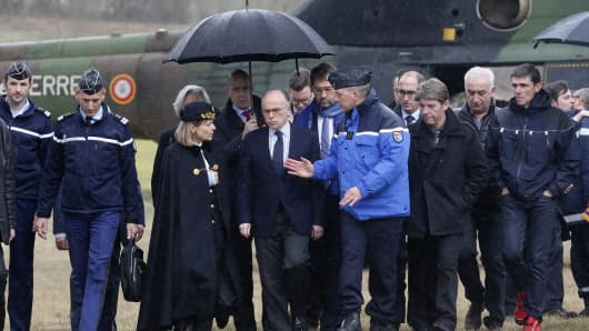 French Interior Minister Bernard Cazeneuve listens to a gendarme after arriving by helicopter on a field next to the crash site of an Airbus A320, near Seyne-les-Alpes, in the French Alps on March 24, 2015.