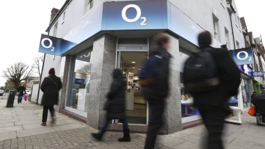 Pedestrians pass an O2 mobile phone store, operated by Telefonica SA, in London, U.K.