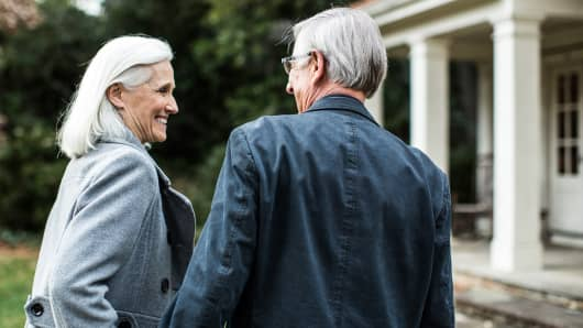 Senior couple walking up to house