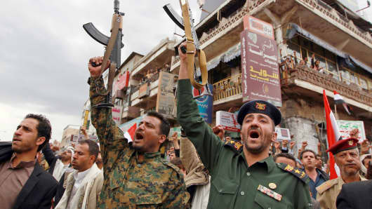 Members of the Yemeni security forces loyal to the Huthi movement brandish their weapons during a gathering in Sanaa, Yemen, March 26, 2015.