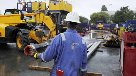 A Cofor worker wearing a safety hard hat moves drilling pipes near to a rig at the geothermal energy drilling site operated by Semhach SA in Villejuif, France.