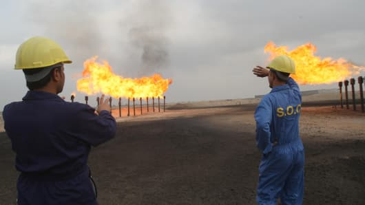 Iraqi Southern Oil Company engineers look towards the flares in the Zubair oil field in southern Iraq.