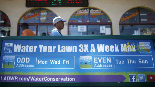 Men walk past a bench with a sign telling people to only water their lawns three times a week, March 24, 2015, in Los Angeles.