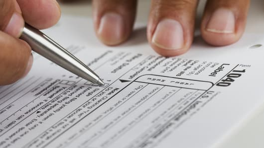 Man filling out income tax form