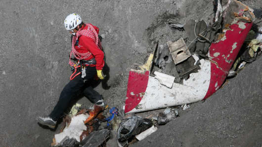 A French rescue worker inspects the remains of the Germanwings Airbus A320 near Seyne-les-Alpes, France.