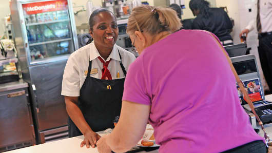 An employee gives a customer her food order inside a McDonald's restaurant in Oak Brook, Ill.