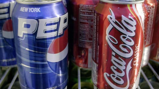 Cans of Pepsi and Coca Cola are shown in a news stand refrigerator display rack in New York.