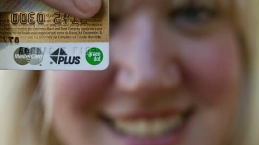 A woman holds her Green Dot prepaid debit card in Monrovia, Calif.