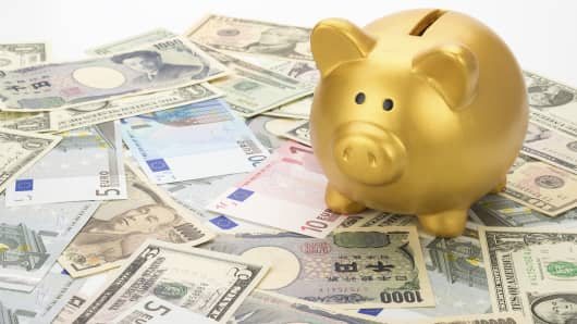 Piggy bank on top of euros, dollars and yen