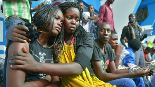 A survivor of an attack by islamist gunmen claimed by al-Shabab on a university campus in Garissa, northern Kenya is comforted by a colleague after arriving in Nairobi on April 4, 2015.