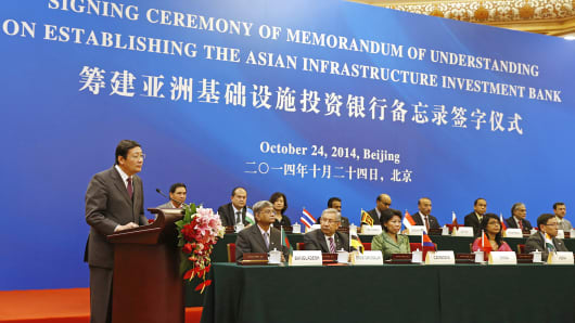 China's Minister of Finance Lou Jiwei, left, delivers a speech next to other representatives of founding member countries at the signing ceremony establishing the Asian Infrastructure Investment Bank in Beijing, Oct. 24, 2014.