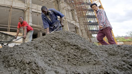 A Chinese contractor walks past Kenyan casual laborers at a construction site in Nairobi, Kenya.