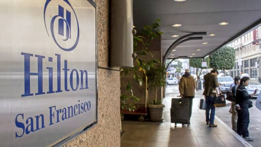 Guests stand outside of a Hilton hotel in San Francisco, Feb. 16, 2015.
