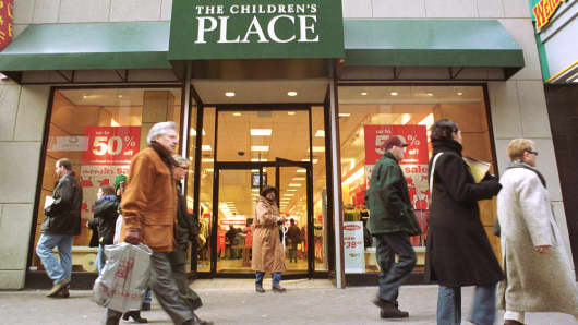 Pedestrians walk passed The Children's Place retail toy store in downtown Boston.