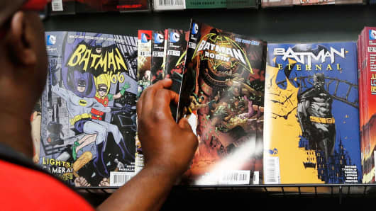 A man reaches for a Batman comic book at a comics store in New York.