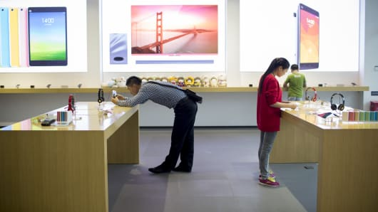Customers look at Xiaomi Corp. products at the company's showroom in Beijing, China