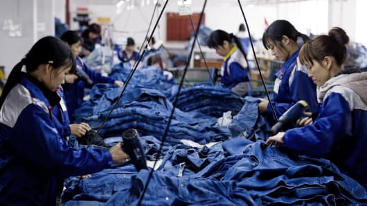 Workers manufacture blue jeans in Congshin textile factory in Xintang, Guangdong province, China.
