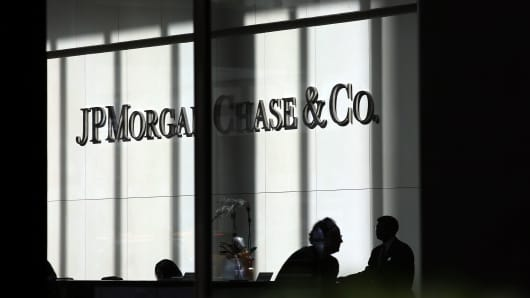 People pass a sign for JPMorgan Chase & Co. at it's headquarters in Manhattan.