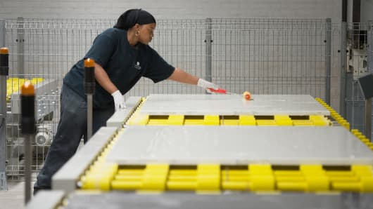 An employee applies a sealant to sheets for countertops at the IceStone manufacturing facility in Brooklyn, New York.