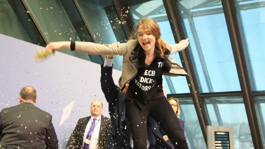 A woman interrupts a press conference by Mario Draghi in Frankfurt, April 15, 2015.