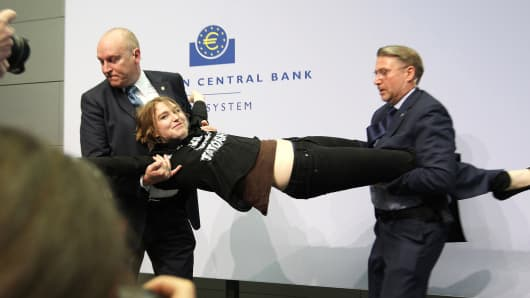 A woman is stopped by security after she interrupted a press conference by Mario Draghi, Frankfurt, April 15, 2015.