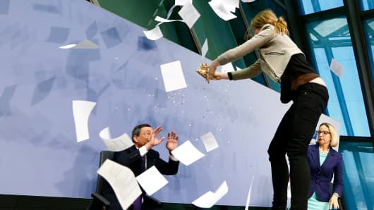 A protester jumps on the table in front of the European Central Bank President Mario Draghi during a news conference in Frankfurt, April 15, 2015.
