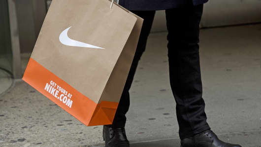A pedestrian with a shopping bag leaves a Niketown store in New York.