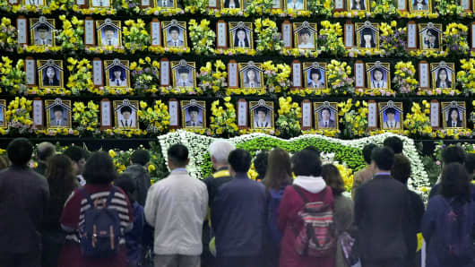 People pay a tribute at a group memorial altar for the victims of the sunken South Korean ferry Sewol at a remembrance hall in Ansan on April 16, 2015.