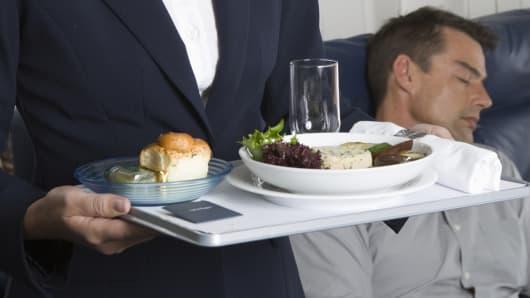 Flight attendant holding tray of food