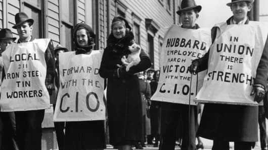 Members of the CIO Local 211 iron, steel and tin workers wear signs supporting the union during a strike in Pittsburgh, circa 1937.