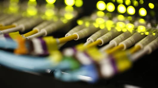 Green LED lights and rows of fibre optic cables are seen feeding into a computer server.
