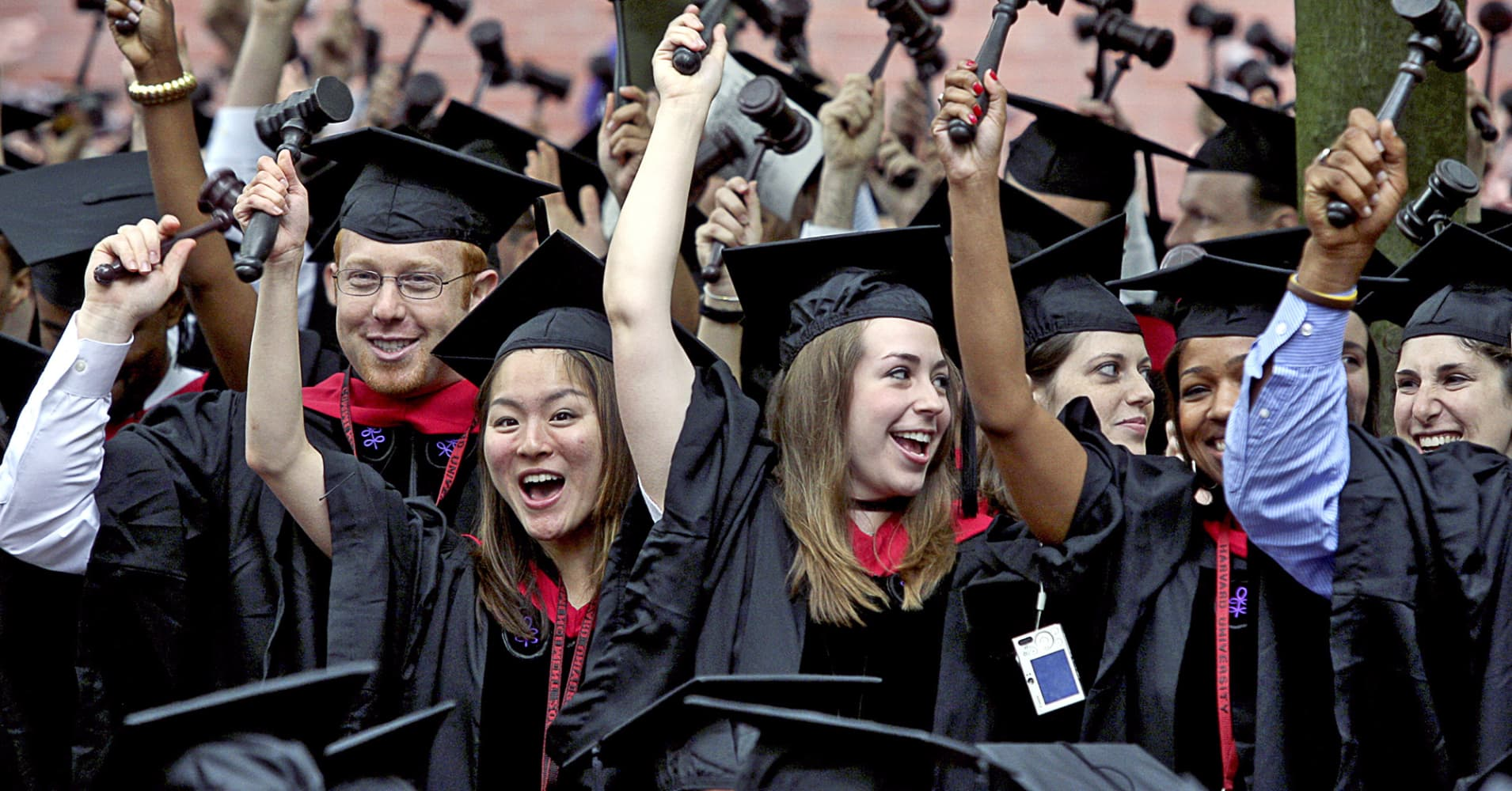 Harvard Law School graduates wave gavels in the air as they celebrate their commencement.