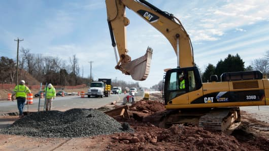 A worker operates a Caterpillar Inc. 336D hydraulic excavator during construction on Route 7 near Falls Church, Virginia.
