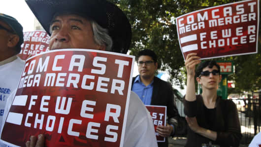 Standing on 4th St. in Los Angeles, Arturo Ortiz, left, from Braceros Unidos de California and Laura Blum-Smith with Writers (cq) Guild of America - West are among a small group of protestors outside the Public Utilities Commission's public comment meeting concerning the proposed Comcast-Time Warner Cable merger on April 14, 2015.