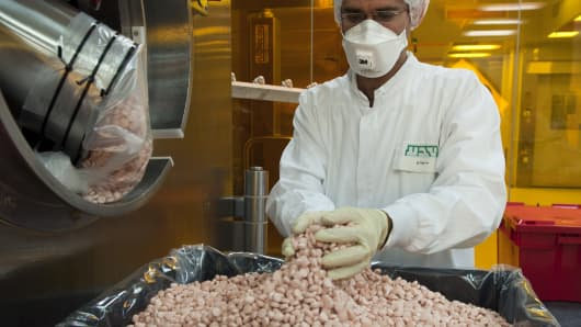 An employee collects newly-manufactured pills from a machine at the tablet production plant at Teva Pharmaceutical Industries Ltd.'s headquarters in Jerusalem Israel