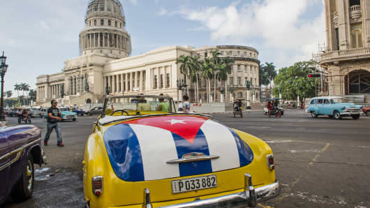 A vintage car with a Cuban flag paint job is parked near the National Capitol Building in Havana on Jan. 7, 2015.