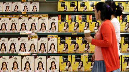 Customers walk past packages of coffee displayed in a shopping mart under Shinsegae in Seoul, South Korea.