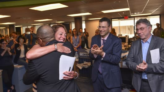 Washington Post reporter Carol D. Leonnig, second left, hugs Managing Editor Kevin Merida, left, as her editor Peter Wallsten, center, and Executive Editor Marty Baron, right, celebrate her Pulitzer Prize award for National Reporting during a gathering at The Washington Post via Getty Images on April 20, 2015 in Washington, D.C.