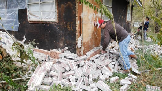 Chad Devereaux examines bricks on Nov. 6, 2011, that fell from three sides of his in-laws' home in Sparks, Oklahoma, after two earthquakes hit the area in less than 24 hours.