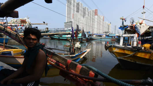 A fisherman sits in his boat with the Green Bay Pluit residential and commercial project in North Jakarta, Indonesia in the background.