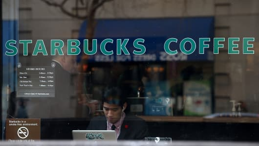 A Starbucks customer works on his laptop inside a Starbucks Coffee shop in San Francisco, California.