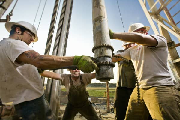 Oil workers using chain to position drill on drilling platform.