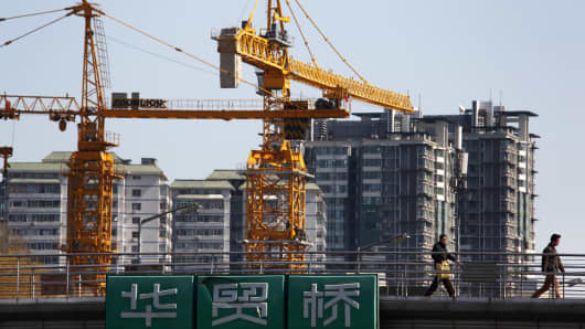 Pedestrians walk past cranes and residential buildings standing under construction in Beijing, China.