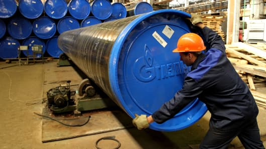 An employee secures a protective cap to a steel pipe destined for OAO Gazprom, produced by OAO TMK at the company's plant in Volzhsky, near Volgograd, Russia.