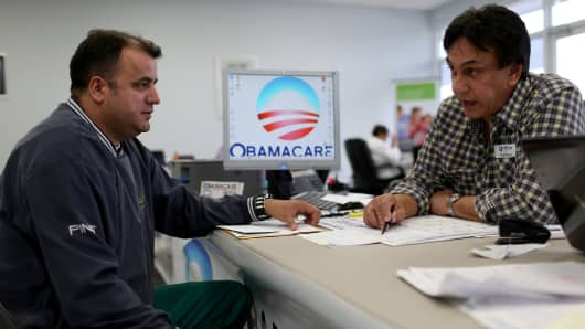 A customer speaks with an insurance agent as he signs up for Affordable Care Act in Miami.